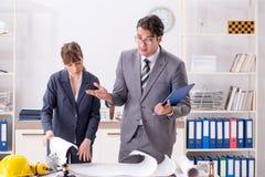 O homem e a mulher que discutem o projeto de construção fotografia de stock