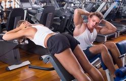 O homem e a mulher que fazer se senta levantam junto usando a máquina no gym foto de stock royalty free