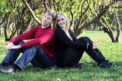 O homem e a mulher sentam-se na grama de volta à parte traseira e aos sonhos no parque Fotografia de Stock