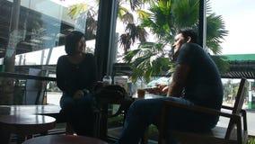O homem e a mulher tailandeses sentam-se para relaxar e falando com café de gelo bebendo na loja do café vídeos de arquivo
