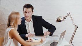 O homem e a mulher trabalham junto no escritório vídeos de arquivo