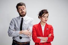 O homem e a mulher tristes de negócio que opõem em um fundo cinzento Imagem de Stock Royalty Free