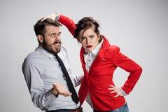 O homem e a mulher tristes de negócio que opõem em um fundo cinzento Fotografia de Stock