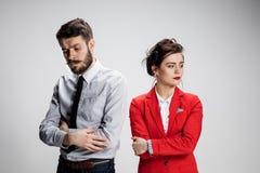 O homem e a mulher tristes de negócio que opõem em um fundo cinzento Imagem de Stock