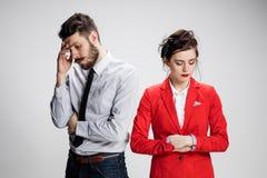 O homem e a mulher tristes de negócio que opõem em um fundo cinzento Foto de Stock