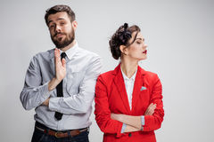 O homem e a mulher tristes de negócio que opõem em um fundo cinzento Imagens de Stock Royalty Free