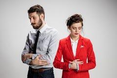 O homem e a mulher tristes de negócio que opõem em um fundo cinzento Imagens de Stock