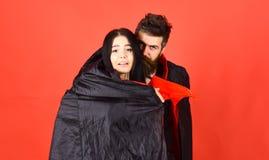 O homem e a mulher vestiram-se como o vampiro, demônio, fundo vermelho Pares em relações do amor, fósforo perfeito Menina na cara imagem de stock royalty free