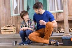 O homem e o menino com os copos do chá têm a conversação Foto de Stock
