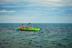 O homem e o menino nadam no caiaque no mar no fundo da ilha Conceito Kayaking Imagem de Stock Royalty Free