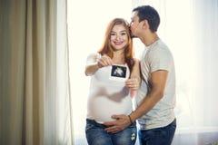 O homem e uma jovem mulher grávida estão esperando uma criança em casa b Imagens de Stock Royalty Free