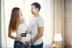 O homem e uma jovem mulher grávida estão esperando uma criança em casa b Imagem de Stock Royalty Free