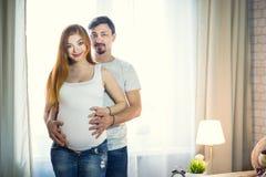 O homem e uma jovem mulher grávida estão esperando uma criança em casa b Imagem de Stock