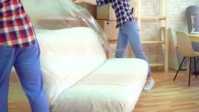 O homem e uma mulher removem o oleado do sofá após mover-se