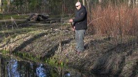O homem elabora a vara de pesca perto do rio video estoque