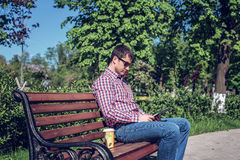 O homem em óculos de sol da camisa e das calças de brim, os olhares video na tabuleta corresponde às redes sociais, no verão ser Foto de Stock