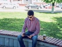 O homem em óculos de sol da camisa e das calças de brim, os olhares video na tabuleta corresponde às redes sociais, no verão ser Imagens de Stock