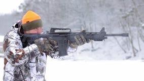 O homem em alvos e em tiros da camuflagem com um rifle tático vídeos de arquivo