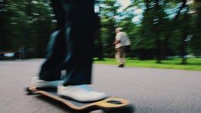 O homem em calças pretas monta no skate na estrada No parque do verão engraçado passatempo filme