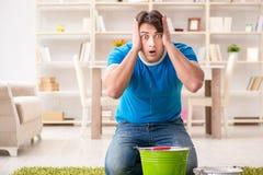 O homem em casa que trata o escape vizinho da inundação imagem de stock royalty free