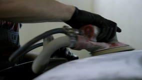 O homem em luvas pretas trabalha com a máquina de lixar do ar no serviço do corpo de carro filme