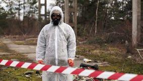 O homem em máscaras do terno e de gás do bio-perigo está atrás da listra no território completamente do desperdício video estoque