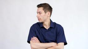 O homem em olhares azuis da camisa por todo o lado no arround ele faz então o sinal silencioso trazendo o dedo a sua boca video estoque