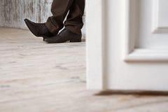 O homem em sapatas pretas em um assoalho de madeira Foto de Stock Royalty Free