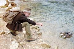 O homem em seu 50s que senta-se pela água e que alimenta ducks Imagem de Stock Royalty Free