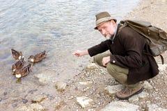 O homem em seu 50s que senta-se pela água e que alimenta ducks Fotografia de Stock Royalty Free