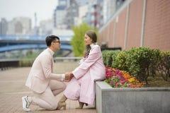 O homem em seus joelhos faz uma proposta para casar a mulher na estrada fotos de stock