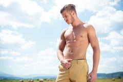 O homem em topless exterior com mão em calças olha para baixo Foto de Stock