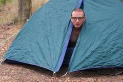 O homem em topless levanta-se na manhã em sua barraca de acampamento Imagens de Stock