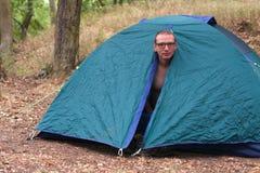 O homem em topless levanta-se na manhã em sua barraca de acampamento Foto de Stock