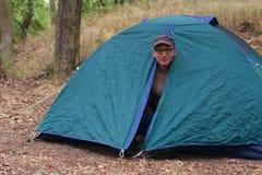 O homem em topless levanta-se na manhã em sua barraca de acampamento Fotografia de Stock
