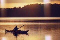 O homem em um barco no lago imagens de stock
