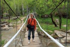 O homem em um bridg da suspensão Imagens de Stock Royalty Free