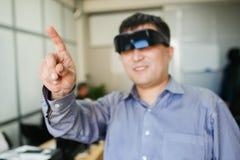 O homem em um capacete da realidade virtual aponta o dedo acima fotografia de stock