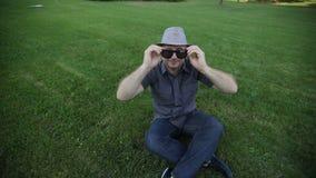 O homem em um chapéu veste óculos de sol em um prado do verão filme