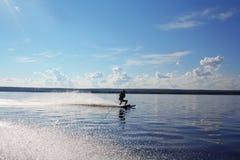 O homem em um esqui de água move-se na água Imagens de Stock