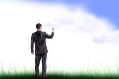 O homem em um terno da obscuridade pinta o céu Foto de Stock