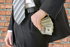 O homem em um terno de negócio pôs o dinheiro em seu bolso Foto de Stock Royalty Free