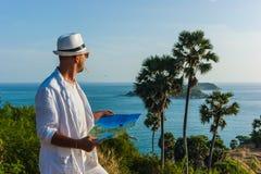O homem em um terno e em um chapéu brancos que sentam-se em uma rocha nos vagabundos do mar Imagens de Stock Royalty Free