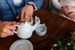 O homem em um terno elegante derrama o chá de um bule em uma caneca Regras de etiqueta em um café O homem toma de uma mulher Um c Fotos de Stock
