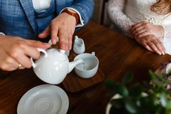 O homem em um terno elegante derrama o chá de um bule em uma caneca Regras de etiqueta em um café O homem toma de uma mulher Um c Imagens de Stock