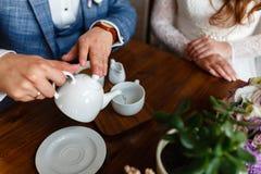 O homem em um terno elegante derrama o chá de um bule em uma caneca Regras de etiqueta em um café O homem toma de uma mulher Um c Imagem de Stock