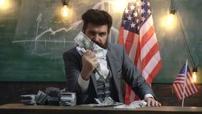 O homem em um terno espreme uma pilha de dinheiro em sua mão com uma expressão má da cara na perspectiva da bandeira dos E.U. video estoque