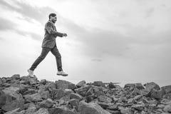 O homem em um terno salta sobre as rochas, dia, exterior imagens de stock