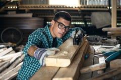 O homem em uma camisa, em óculos de proteção e em luvas de manta verifica a qualidade da placa de planeamento na oficina, trabalh Imagem de Stock Royalty Free