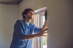 O homem em uma camisa azul faz a instalação da janela fotos de stock